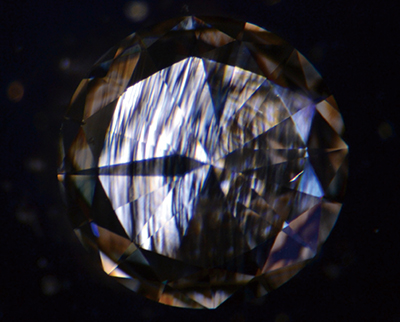Fig.5 CVD合成ダイヤモンドの交差偏光下の歪複屈折。低次の白黒のコントラストの干渉色による筋状模様が見られる。