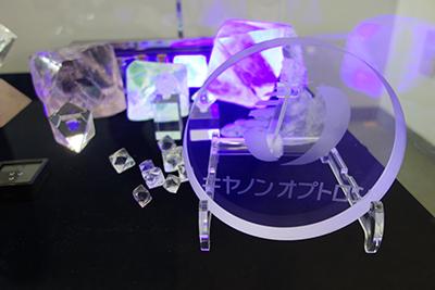 写真4:展示されている合成蛍石の大小様々な劈開片と社名盤。ブラックライトの照射で蛍光していることがわかる