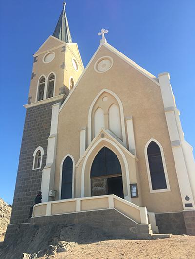 Felsenkirche の外観(左)と祭壇(右)。ダイヤモンドヒルの高台に立つ教会。Albert Bauseが1911年後半に着工開始、1912年に完成。Albert Bauseがケープタウンで見たビクトリア朝の建物の影響を受けている。祭壇の上にあるステンドグラスのパネルはKaiser Wilhelm2世によって寄贈され、聖書はKaiser Wilhelm2世の妻からの贈り物