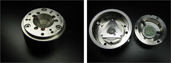 図3:研究室で使用しているダイヤモンドアンビルセル。外形は約70 mm。(左)セルの外観。3本のネジで加圧していく。(右)セルの内部。上下に1対のダイヤモンドアンビルが装着されている