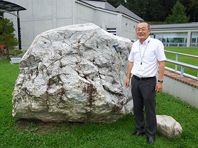 写真4–a:ミュージアム館外に展示されているヒスイの巨礫と学芸員の竹之内博士